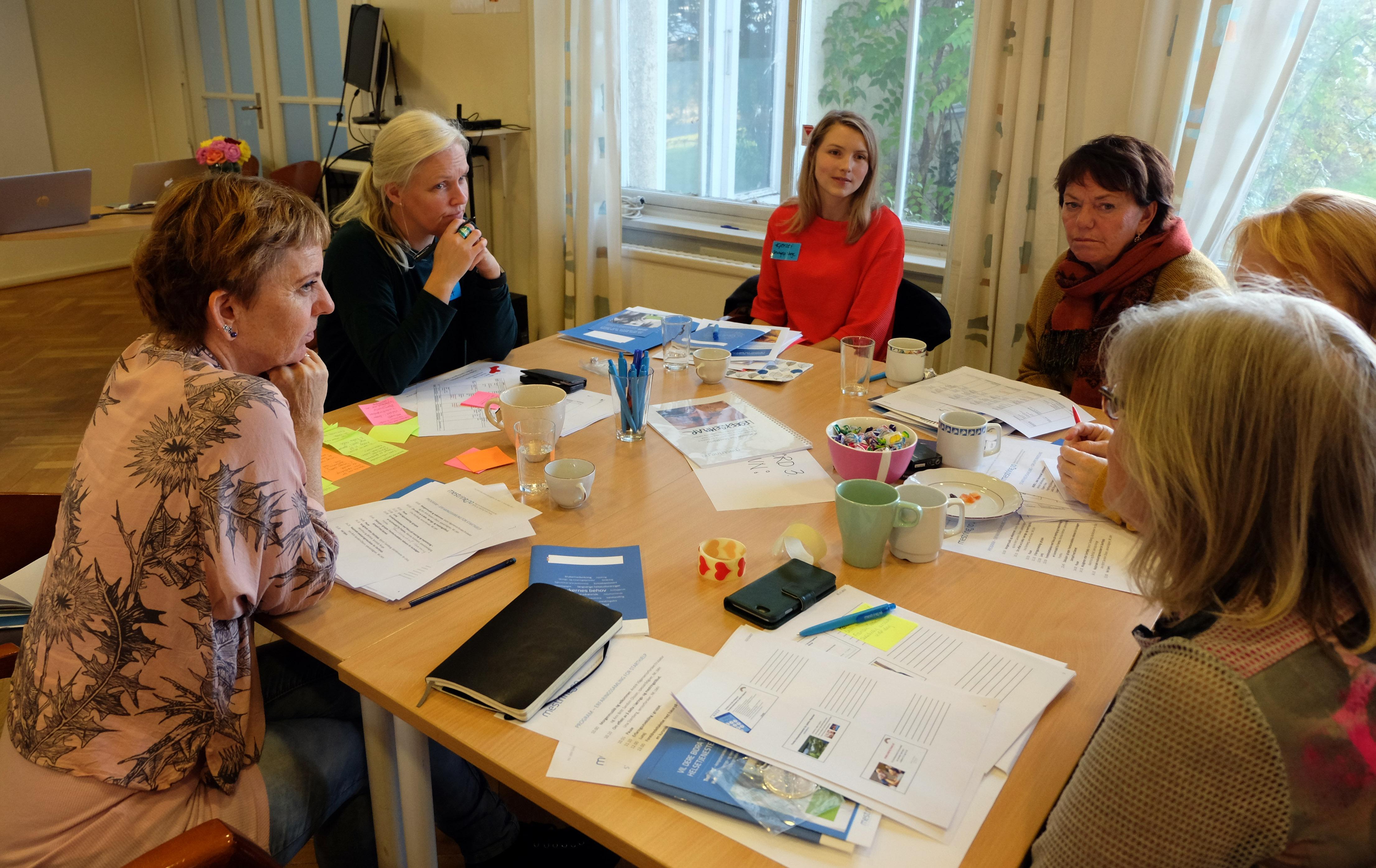 Bilde av en gjeng rundt et bord som samarbeider under samlingen.