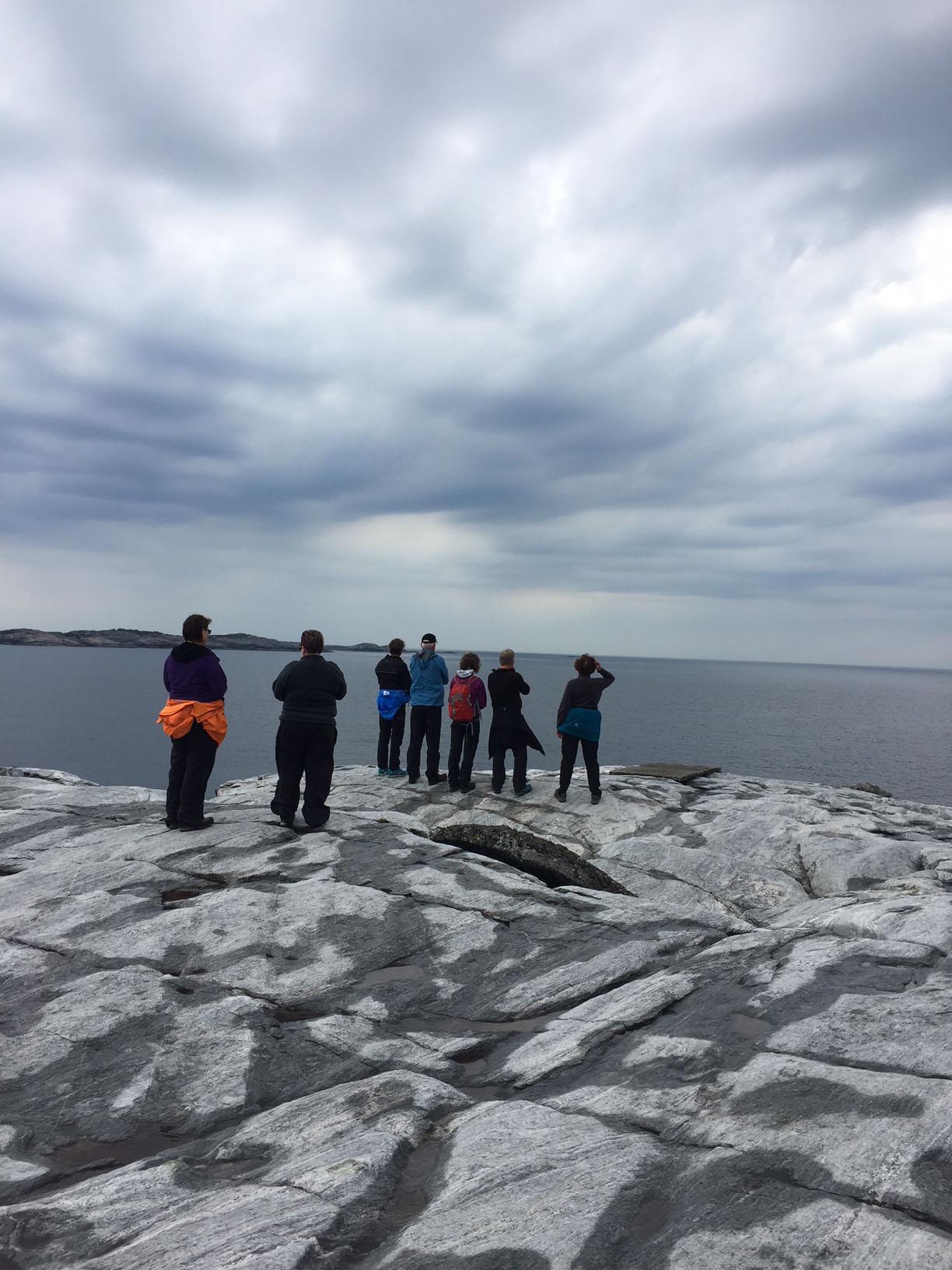 Naturbilde med mennesker hav, svaberg og himmel