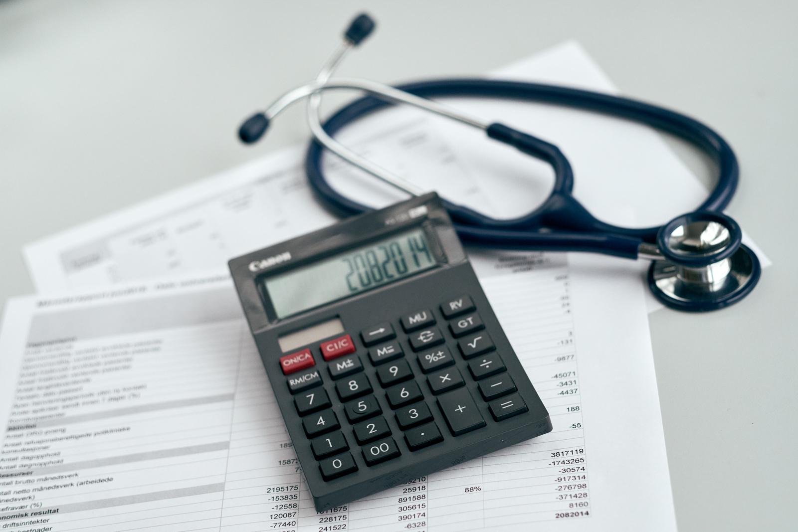 Bilde av kalkulator, stetoskp og regneark.